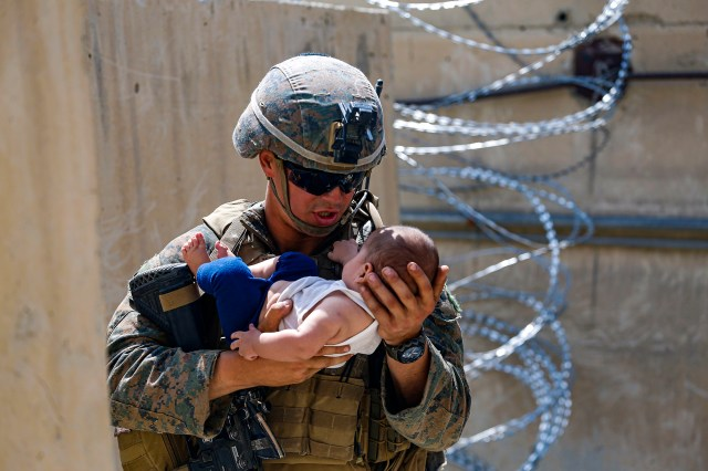 A US Marine comforts an infant while they wait for the mother during an evacuation at Hamid Karzai International Airport, in Kabul, Afghanistan.