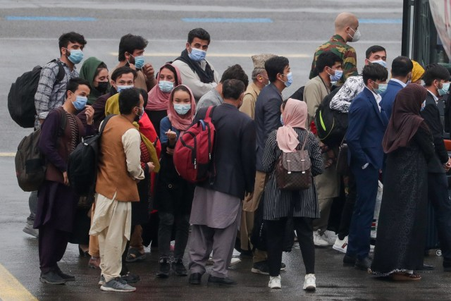 People line up to board a bus after disembarking an Air Belgium evacuation flight arriving from Afghanistan at Melsbroek Military Airport, on August 23, 2021