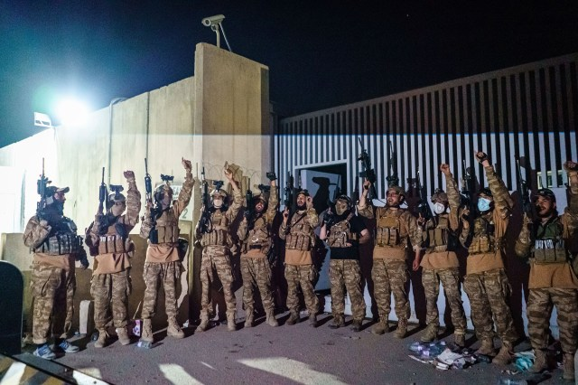 Taliban fighters from the Fateh Zwak unit celebrate before storming into the Kabul International Airport.