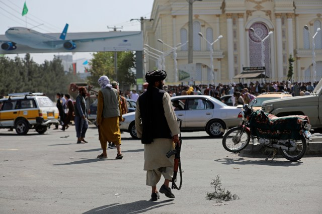 Taliban fighters stand guard in front of the Hamid Karzai International Airport, in Kabul, Afghanistan, Monday, Aug. 16, 2021.
