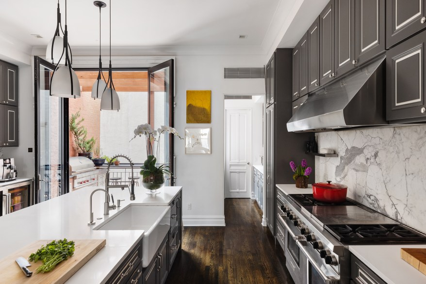 The kitchen has a pantry, cabinets, Caesarstone countertops and a marble backsplash.