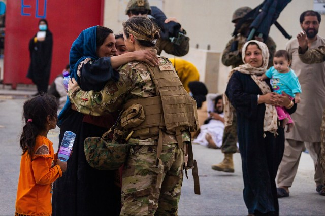 An Afghan mother embracing an U.S. soldier after reuniting her family at Hamid Karzai International Airport on August 20, 2021.