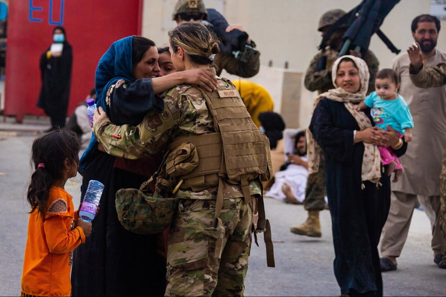 An Afghan mother embraces a US soldier after reuniting her family at Hamid Karzai International Airport on August 20, 2021.
