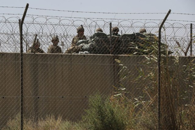 Military standing by a fence.