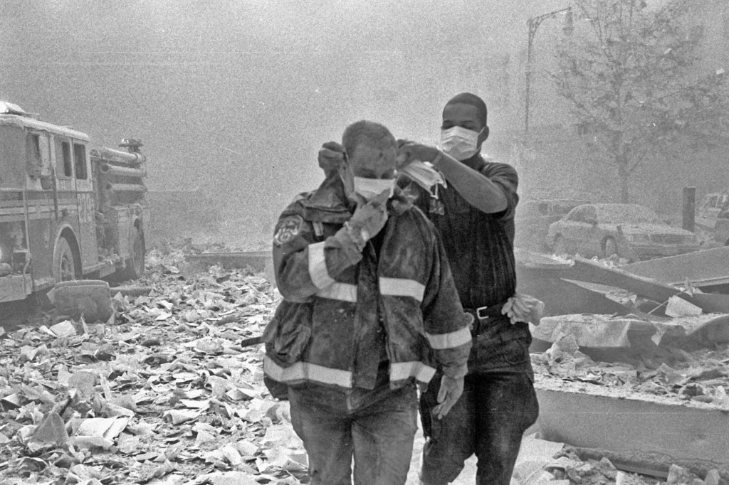 First responders cover their faces to block out the dust.