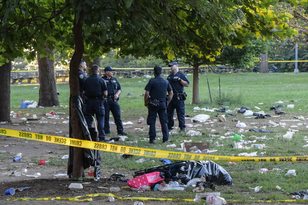 NYPD officers at the scene of the fatal shooting in Claremont Park in the Bronx.