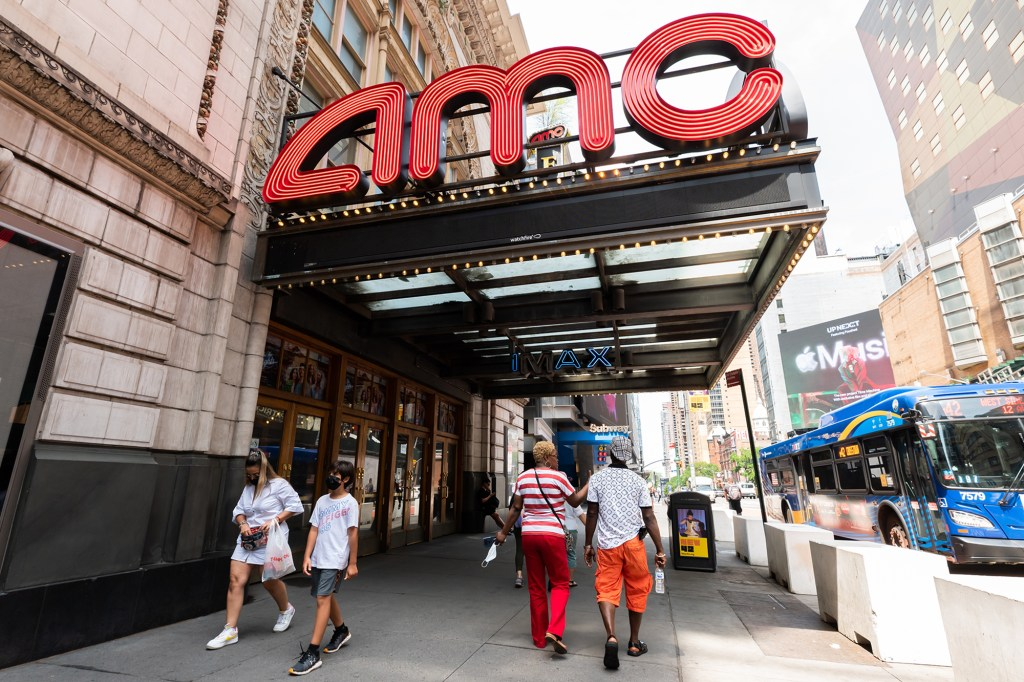 People walk outside AMC Empire 25 movie theater in Times Square