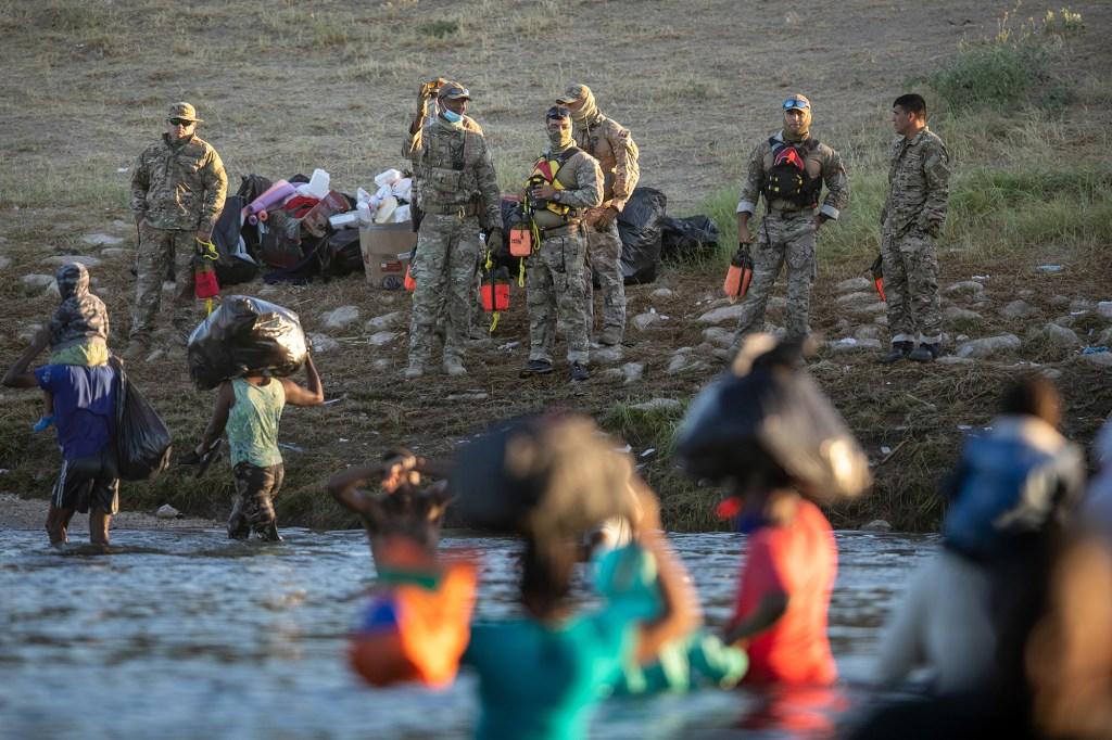 US Border Patrol watch migrants cross into the United States through the Rio Grande River.