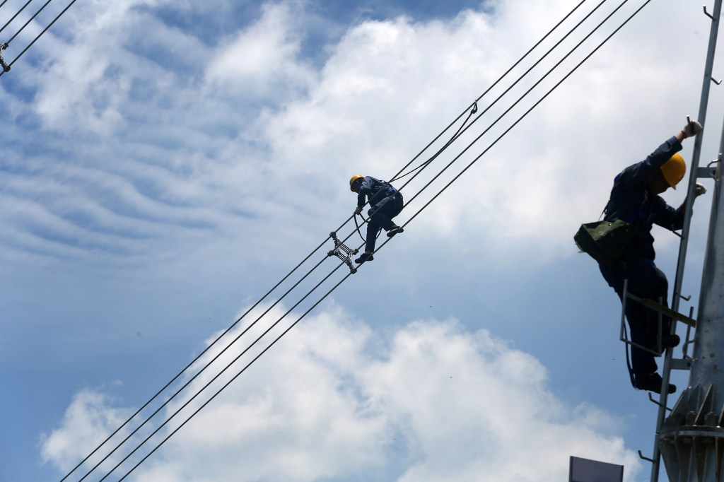 Workers of grid operator China Southern Power Grid inspect power cables connecting transmission towers.