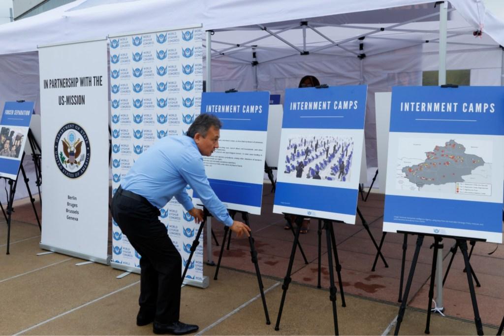 DolkunIsa,President of the World Uighur Congress sets up the display at the Uighur photo exhibit.