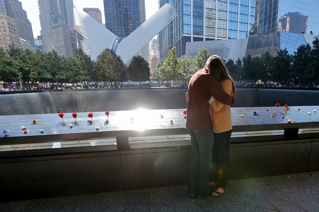 A couple mourns at the North reflecting pool during the 20th anniversary ceremony of the September 11 terrorist attacks.