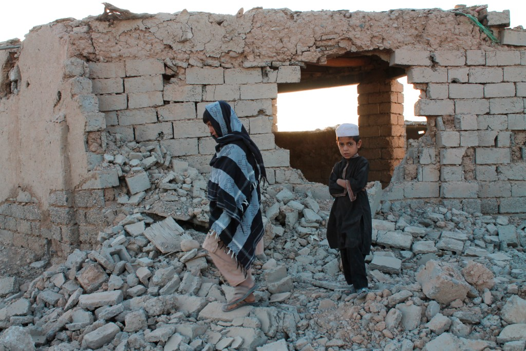 Afghan boys walk near a damaged house after airstrikes in two weeks ago during a fight between government forces and the Taliban in Lashkar Gah, Helmand province, southwestern, Afghanistan, Saturday, Aug. 21, 2021.