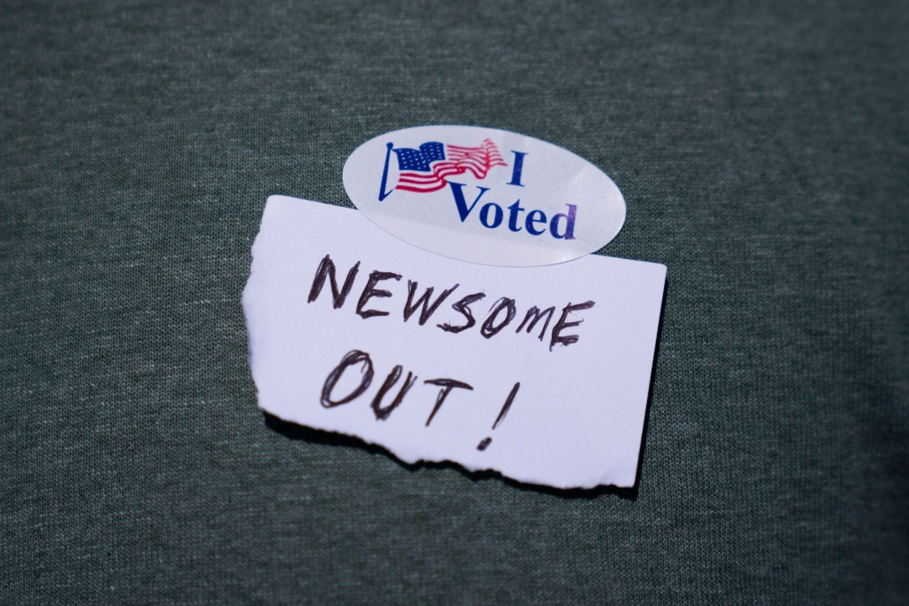 """33.2 percent voted """"yes"""" to recall Gavin Newsom. One voter wrote """"NEWSOME (sic) OUT!"""" on a slip of paper and placed it underneath their voter sticker."""
