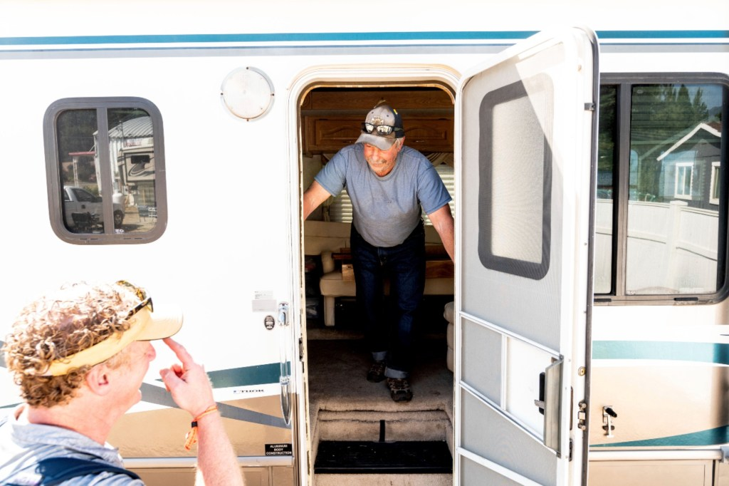 olunteer firefighter John Hunter looks out from a donated motorhome he received from Woody Faircloth, left, on Sunday, Sept. 5, 2021, in Quincy, Calif.