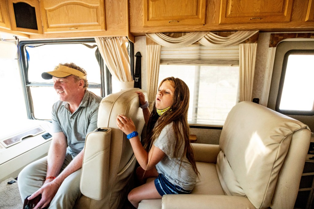 Woody and Luna Faircloth sit in a donated RV before delivering it to a Dixie Fire victim on Sunday, Sept. 5, 2021, in Sierra County, Calif.