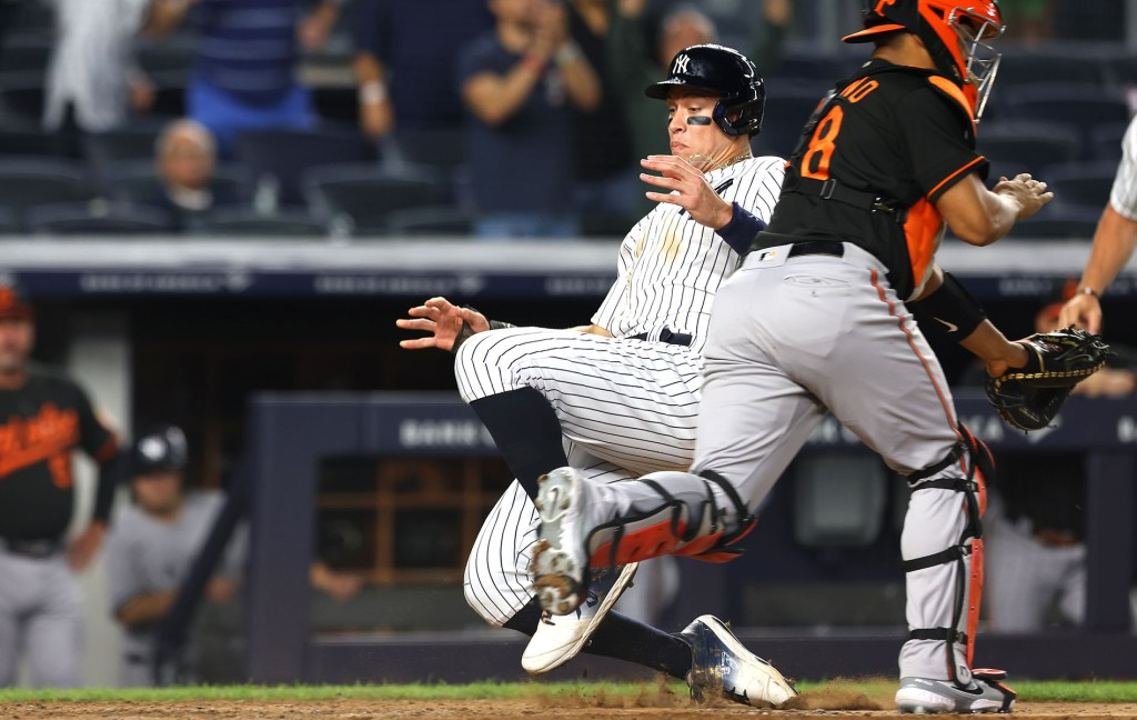 Aaron Judge slides safely into home to score the game-winning run in the Yankees' 4-3, 11-inning victory over the Orioles.