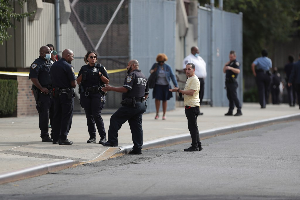 Authorities investigate the scene of the alleged stabbing outside Harry Truman High School in the Bronx.