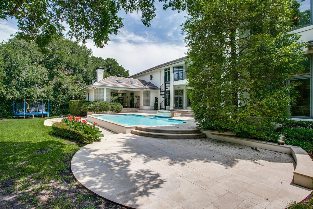 The gated 0.93-acre lot has a four-car garage, a pool, a covered outdoor dining area and a sunning area, listing photos show.