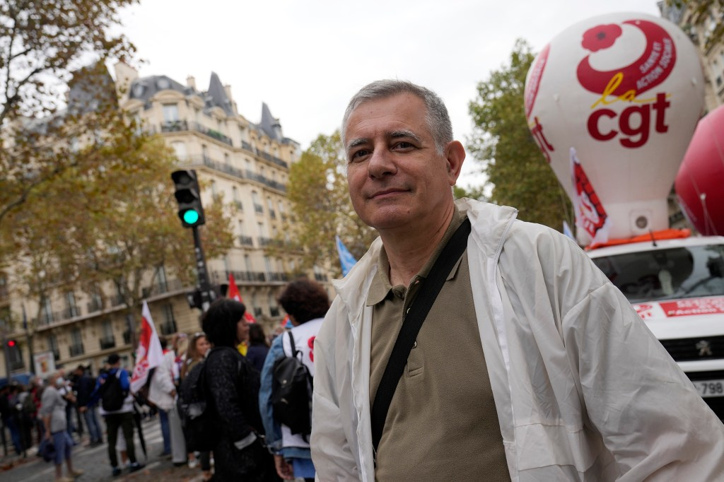Medical Doctor Christian Prudhomme attends a protest gathering outside the Health Ministry, in Paris, Tuesday, Sept. 14, 2021 against a law requiring them to get vaccinated by Wednesday or risk suspension from their jobs.