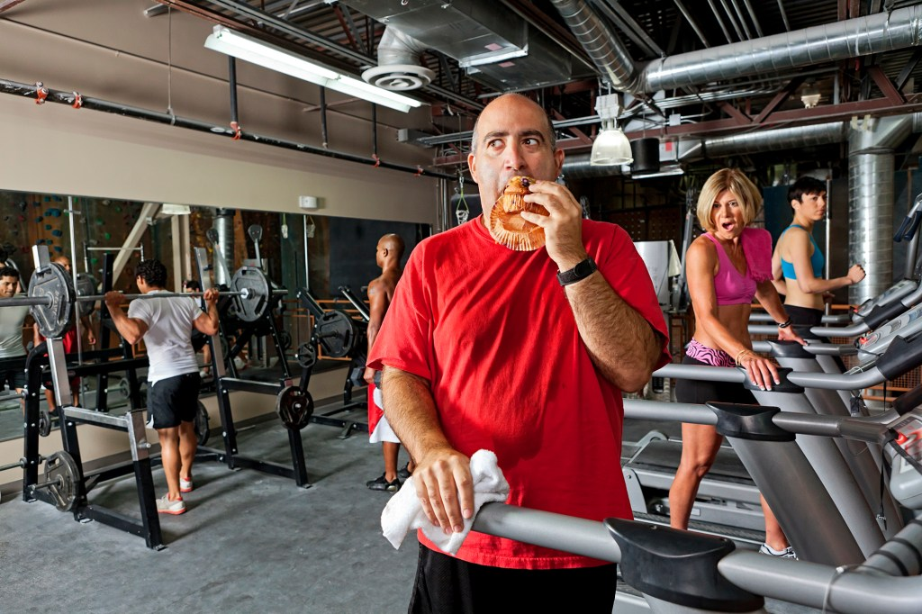 A man eats a pastry at the gym.