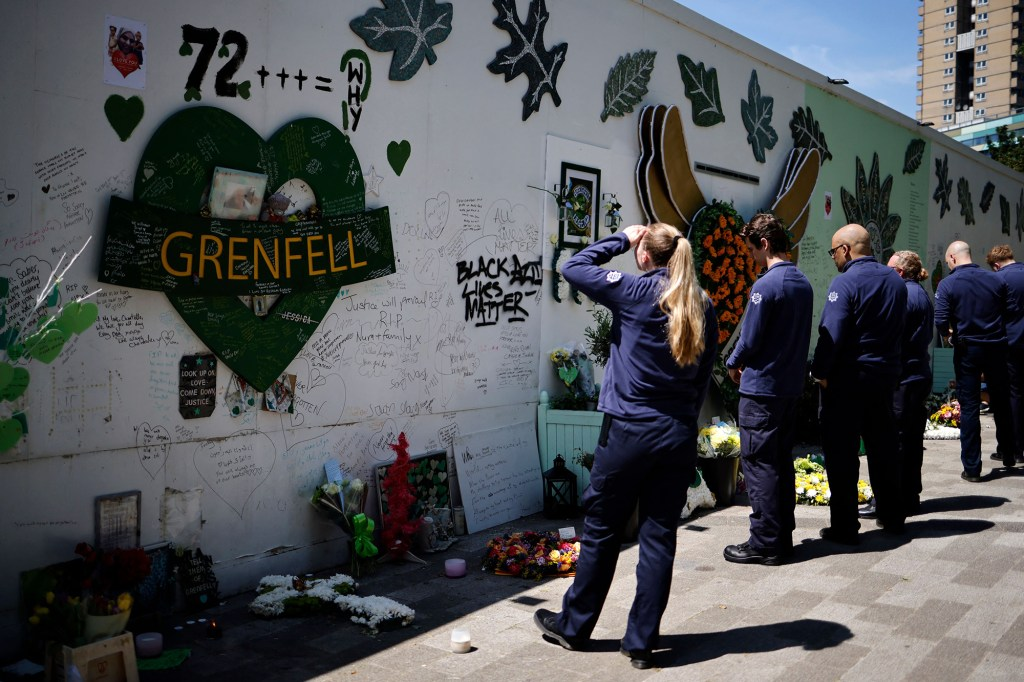 Firefighters visit a memorial set up for the victims of the Grenfell Tower fire.