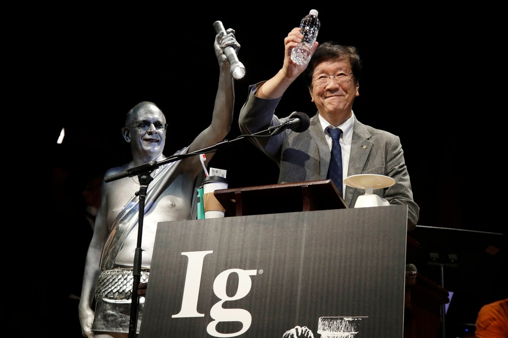 In this Sept. 12, 2019 file photo, Shigeru Watanabe, of Japan, receives the Ig Nobel award in chemistry for estimating the total saliva volume produced per day by a typical five-year-old, at the 29th annual Ig Nobel awards ceremony at Harvard University, in Cambridge, Mass.