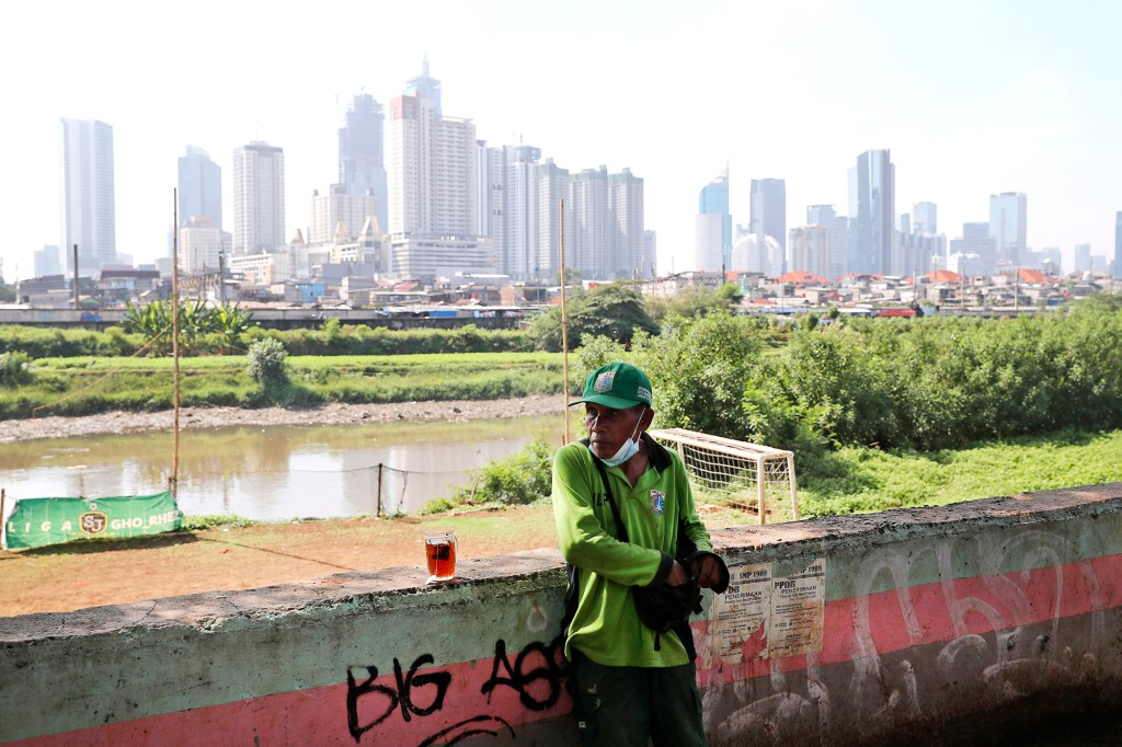 A municipal worker takes a break as the hazy city skyline is seen in the background in Jakarta, Indonesia, Thursday, Sept. 16, 2021.