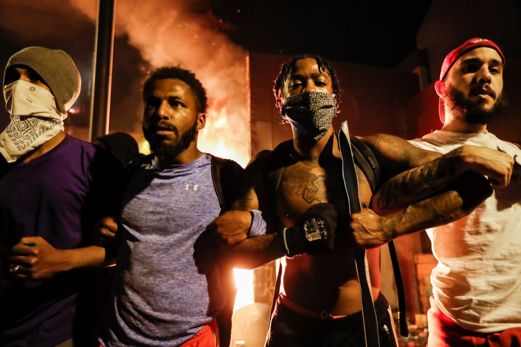 Protestors demonstrate outside of a burning Minneapolis 3rd Police Precinct in Minnesota on May 28, 2020.