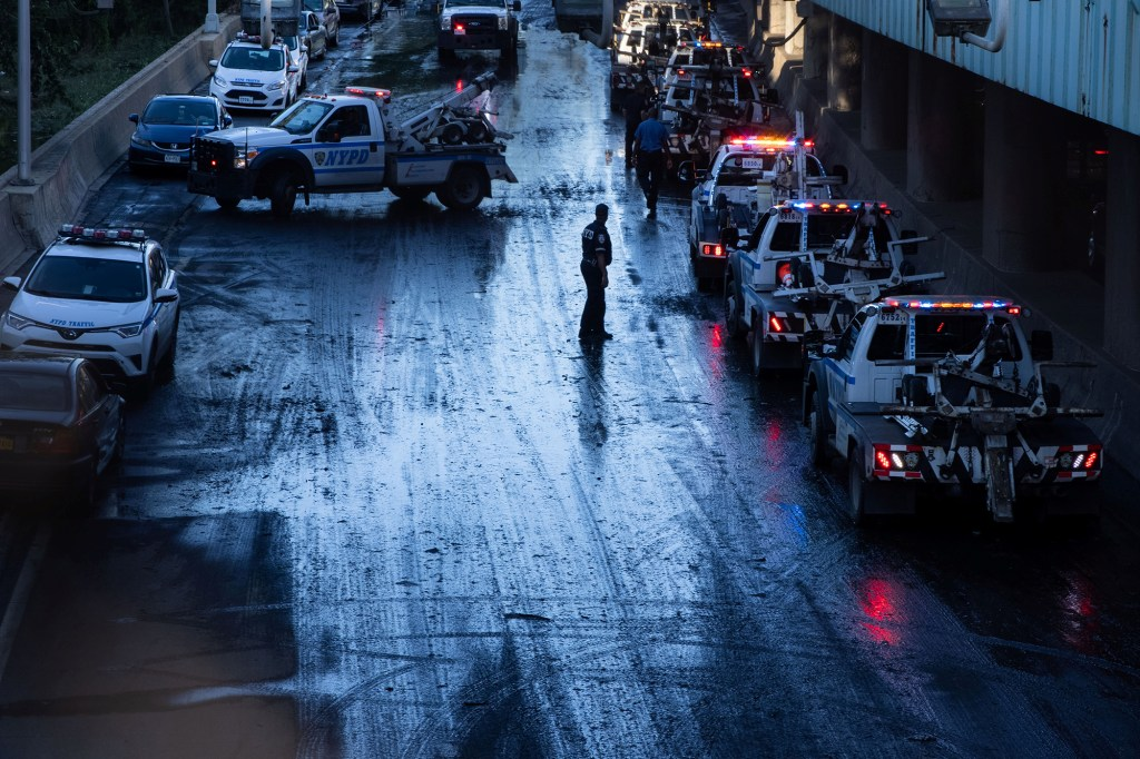 A member of the NYPD supervises tow trucks clearing cars abandoned on the Major Deegan Expressway after the remnants of Tropical Storm Ida brought drenching rain, flash floods and tornadoes to parts of the northern mid-Atlantic, in the Bronx borough of New York City, U.S., September 2, 2021