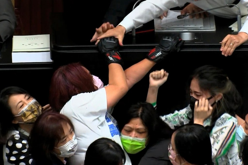 In this image taken from video by Taiwan's EBC, opposition Nationalist party lawmaker Chen Yu-jen, in white shirt, is grabbed by ruling Democratic Progressive Party lawmakers as she tries to climb onto the podium during a parliament session in Taipei, Taiwan, Tuesday, Sept. 28, 2021.