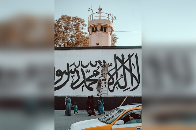 Afghan painters paint the Taliban slogan at the front of the US Embassy.