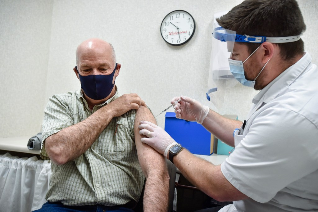 FILE - In this April 1, 2021, file photo Gov. Greg Gianforte receives a shot of the Pfizer COVID-19 vaccine from pharmacist Drew Garton at a Walgreen's pharmacy, in Helena, Mont.