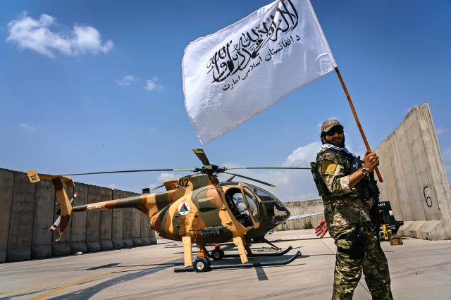 Taliban fighter raises the movement's flag.