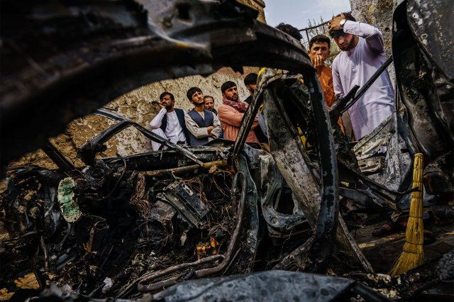 Relatives and neighbors of the Ahmadi family gathered around the incinerated husk of a vehicle.