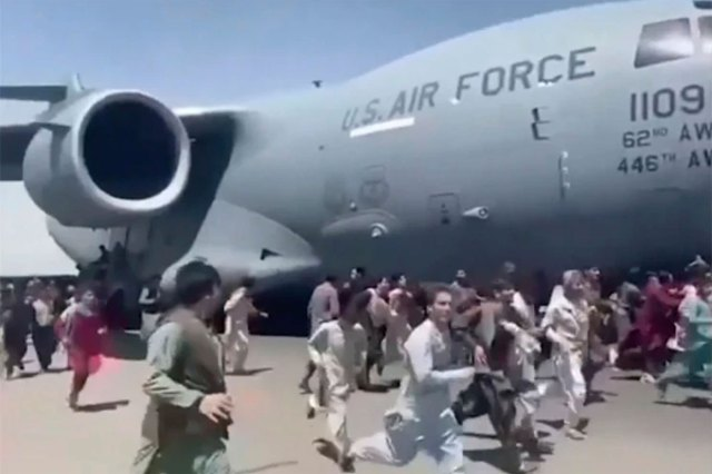 Thousands of Afghans desperately chase and cling onto a US Air Force plane flying up the runway.