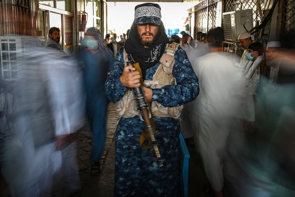 A Taliban fighter stands guard as people move past him at a market with shops dealing with currency exchange in Kabul on September 5, 2021.