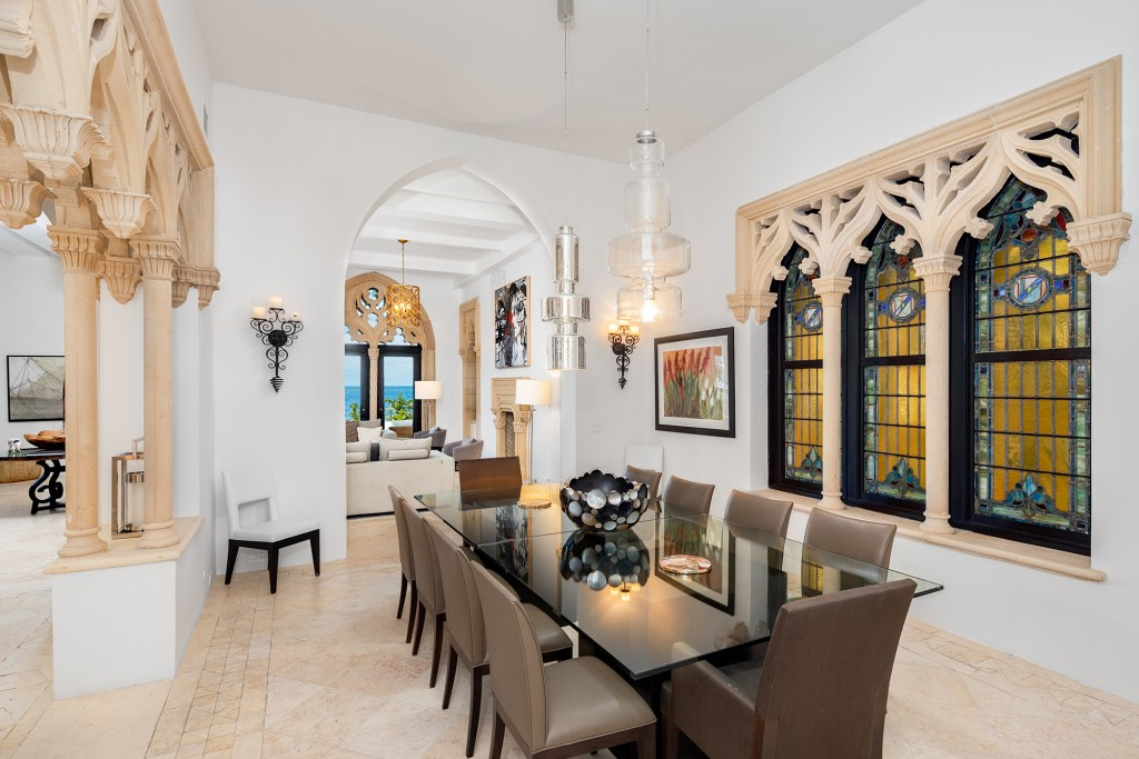Stone tracery decorates arched stained glass windows in the dining room.