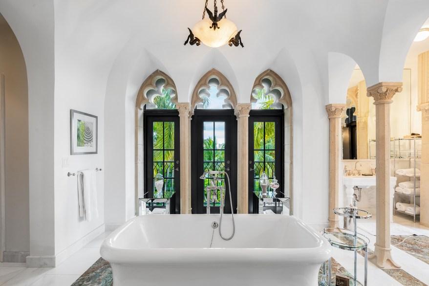 The standalone bathtub is set against three arched windows.