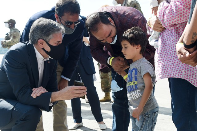 Secretary of State Antony Blinken shows a picture of his children to a young Afghan refugee at Ramstein Air Base in Germany.
