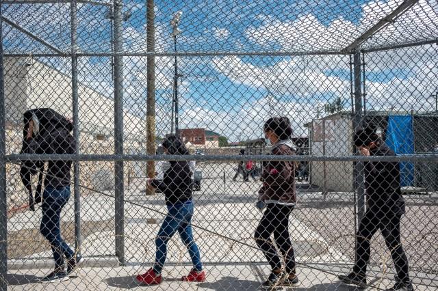 Migrants walk through the El Paso Del Norte Processing Center as they are expelled to Ciudad Juárez,