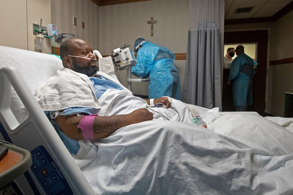 Cedric Daniels, 37, of Gonzales, La., rests in his room, recovering from COVID-19 at Our Lady of the Lake Regional Medical Center in Baton Rouge.