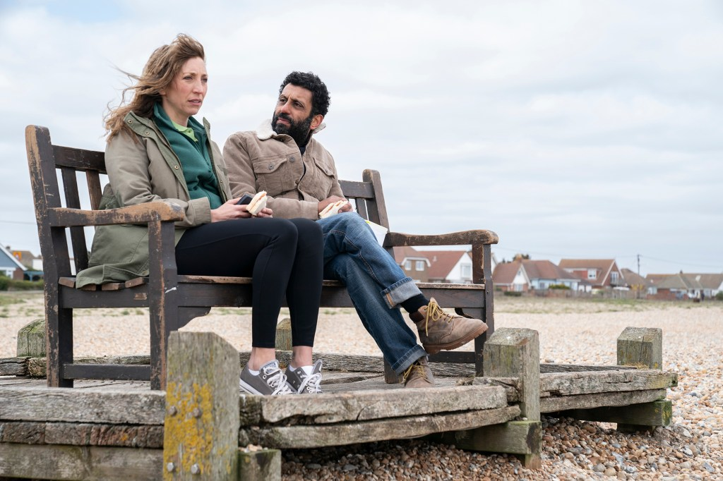 Photo showing Daisy Haggard and Adheer Akhtar as Miri and Billy, sitting on a wooden bench on a rocky beach.