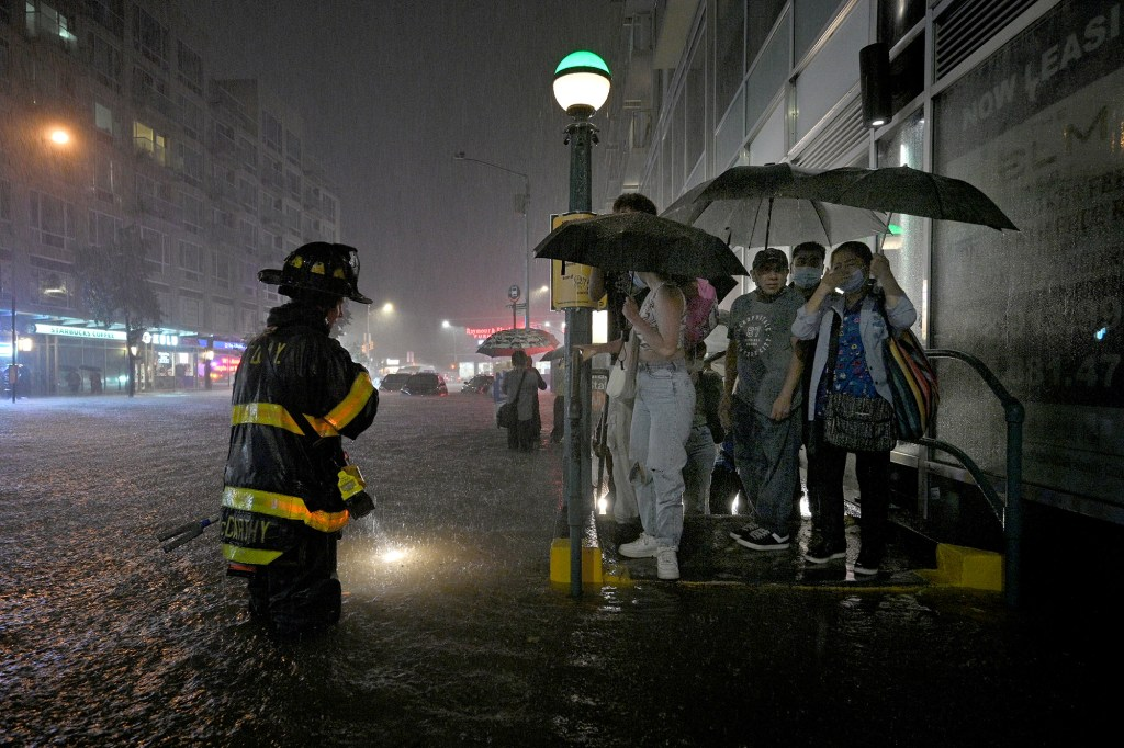 A member of the FDNY directs people stranded at a subway entrance during flash flooding caused by storm Ida in the New York City.