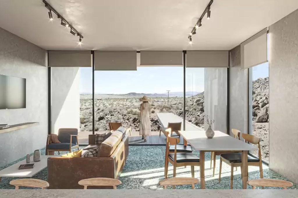 The minimalist living space with floor-to-ceiling windows looking out to the Mojave Desert.