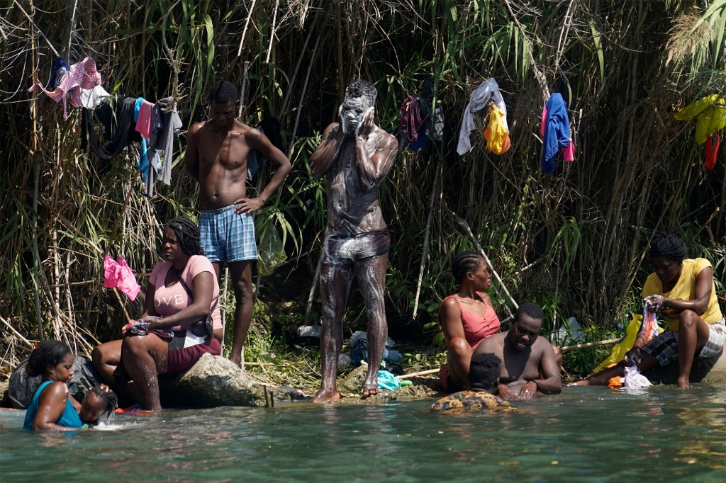 Haitian migrants bathe and do laundry along the banks of the Rio Grand after they crossed into the United States.