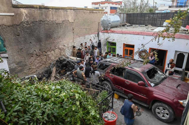 Afghan residents and family members of the victims gather next to a damaged vehicle.
