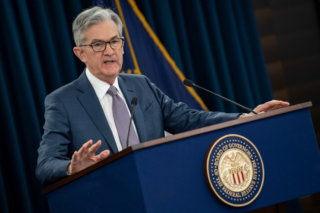 Fed Chairman Jerome Powell standing at a podium with two microphones and the Federal Reserve seal on the front