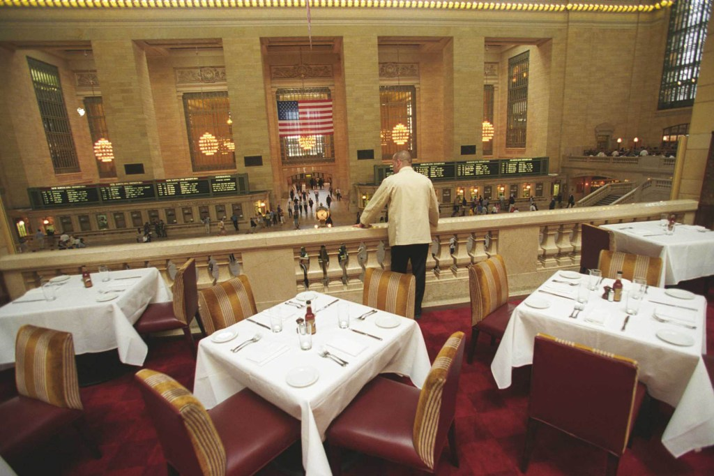 A waiter looking over the balcony at Michael Jordan's Steak House NYC.