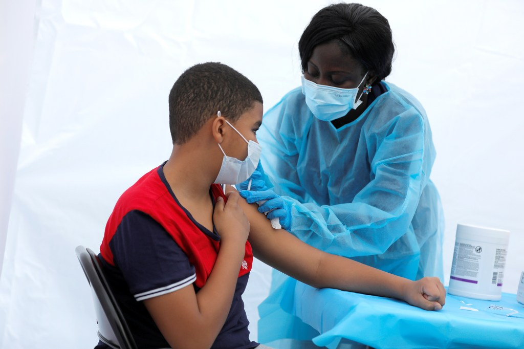 12-year-old Justin Concepcion receives a dose of the Pfizer-BioNTech vaccine.