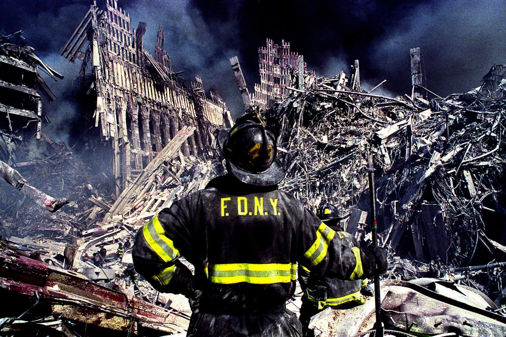FDNY firefighter Matthew Long stands with pike in hand looking over the total devastation that remains of the New York City Twin Towers, which only hours earlier were stuck by two passenger airliners.